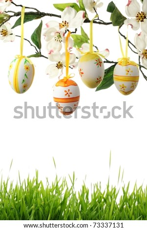 Easter Eggs hanging on branch with green grass border. - stock photo