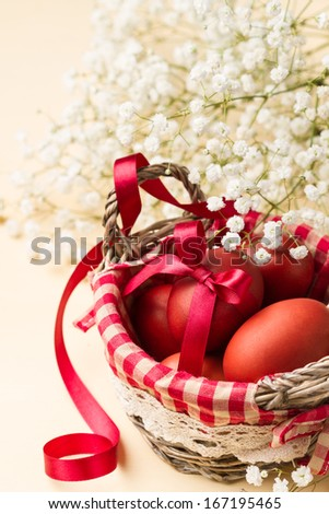 Easter eggs in a basket with red checkered napkin and white flowers (vertical shot) - stock photo