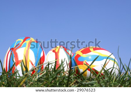 3 Easter eggs in grass against  a bright blue sky