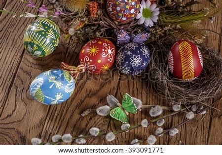 easter eggs in the nest, decorative butterfly, flowers and blooming willow on the wooden background. easter decoration. happy easter - stock photo