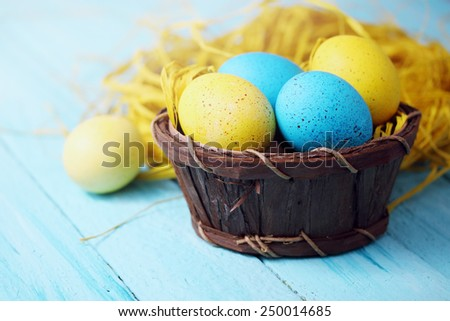 Easter still life in shades of yellow, nest with eggs - stock photo