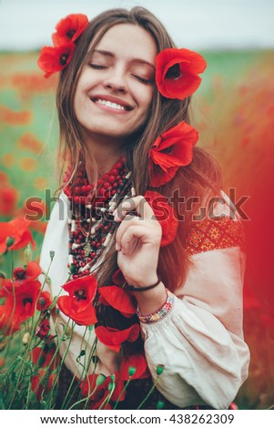 ?eautiful girl in the poppy field. Ukrainian national clothes