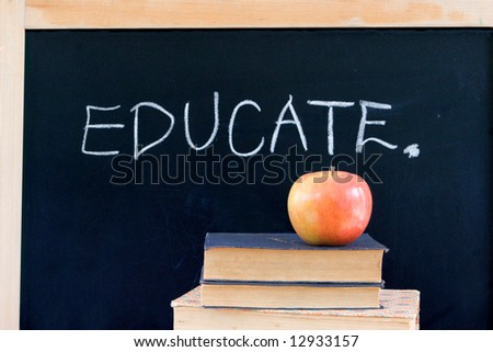"""""""EDUCATE"""" written on chalkboard with red apple & books - stock photo"""