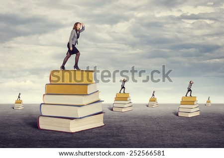 Education. Businesswoman looking into the distance while standing on the foot of books. - stock photo