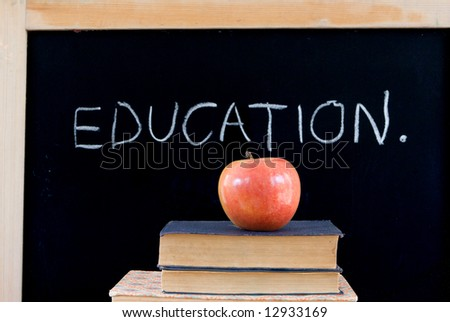 """""""EDUCATION"""" written on chalkboard with red apple & old books - stock photo"""