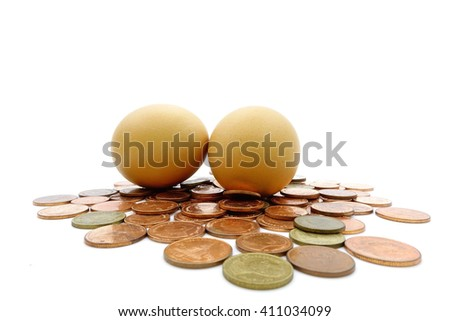 Egg  over many thai baht coins on a white background:select focus with shallow depth of field:Macro shot. - stock photo