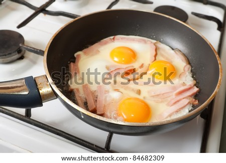 eggs and bacon on hot skillet. One of the stages of preparation of bacon and eggs.  See series - stock photo