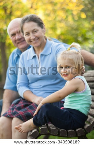 elderly grandparents with cutes grandchild     in autumn park.