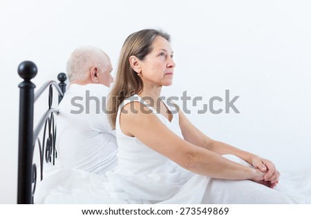 elderly man and   middle-aged woman sorting out their relationships   in   bedroom. - stock photo