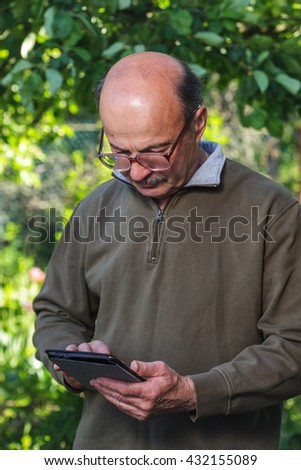 Elderly man with a bald head, mustache and glasses learn to deal with tablet. Modern technologies on holiday or vacation. Maintain a relationship with families at a distance - stock photo