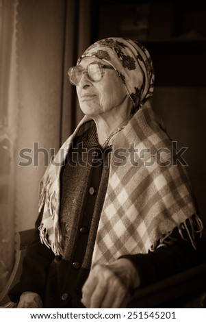 elderly woman in   scarf and  glasses near window at home. - stock photo