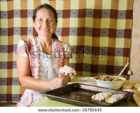 elderly  Woman making russian meat dumplings at kitchen - stock photo