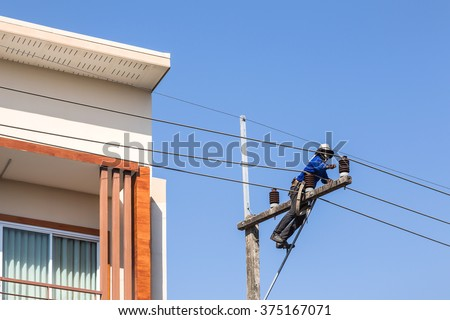 electrician installing wire on electric power pole in to house on blue sky background. - stock photo