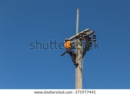 electrician working on electric power pole on blue sky background.