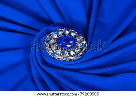 elegant blue fabric with brooch - stock photo