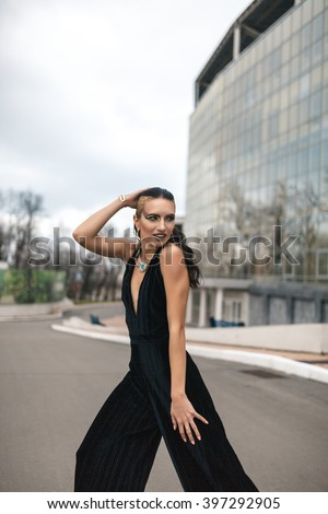 Elegant female with beautiful makeup and hairstyle posing during her walk. She is wearing a fancy black pants. Lady is standing with her back to a modern building