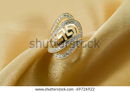 Elegant jewelry ring with jewel  brilliants on a background of golden silk - stock photo