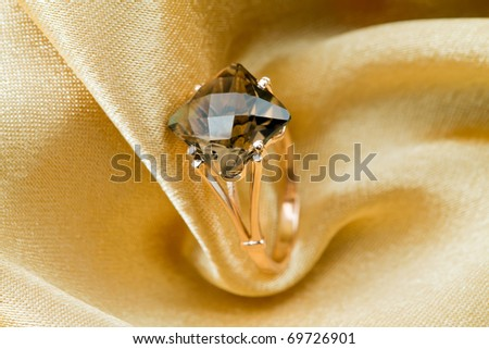Elegant jewelry ring with jewel topaz  on a background of golden silk - stock photo