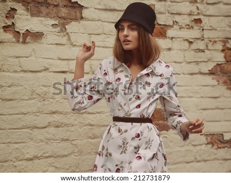 Elegant woman in a Trendy Cap and Old-fashioned Clothing. with noise added - stock photo