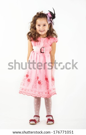 Elegant young girl child in frock striking stylish pose.