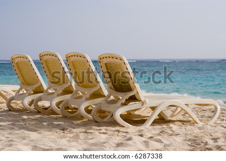 4 empty loungers on a tropical beach (Punta Cana, Dominican Republic) - stock photo