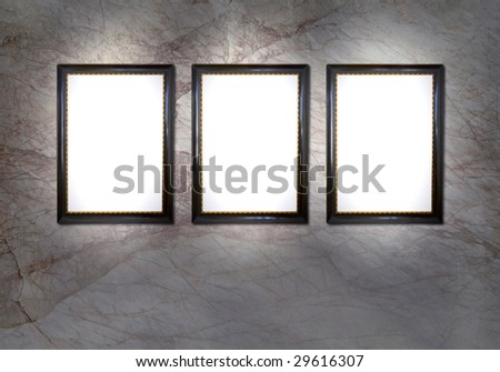 3 empty picture frames with spotlights against a marble wall, design template, free copy space - stock photo
