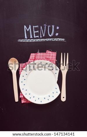 "empty plate and ""menu"" inscription on a black background"