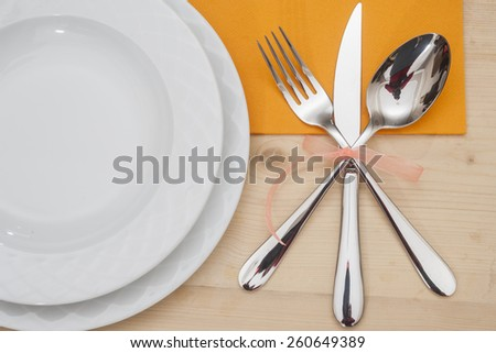 Empty plates with fork, spoon and knife on a wooden table - stock photo
