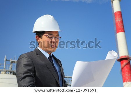engineer oil refinery checking plan on location site with tower and blue sky background - stock photo