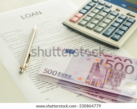500 euro banknote laying on loan document with pen and calculator on the desk of the bankers. - stock photo