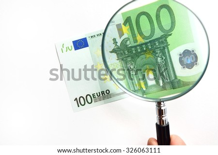 100 euro banknote under the Magnifying glass - stock photo