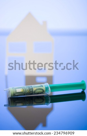 100 Euro banknote wrapped in syringe, Model house in background - stock photo