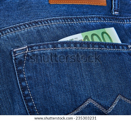 100 Euro bill sticking out from a blue jean pocket. Closeup - stock photo