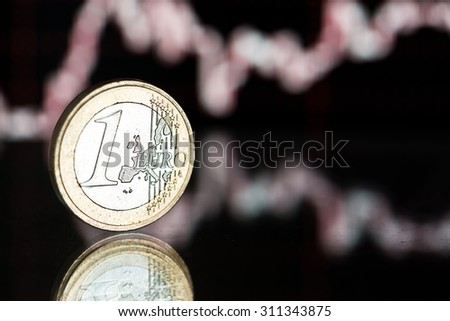 euro coin. Fluctuating graph on black background. Rate of the euro (shallow DOF)  - stock photo