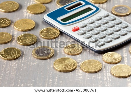Euro coins and digital calculator on wooden background - stock photo