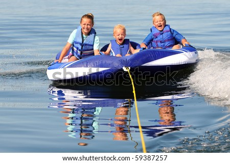 3 Excited Kids Riding Water Tube - stock photo