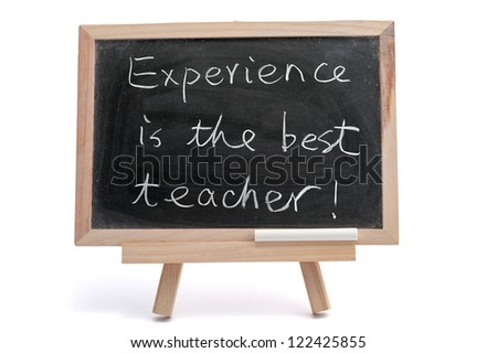 """""""Experience is the best teacher"""" saying written on blackboard over white background - stock photo"""