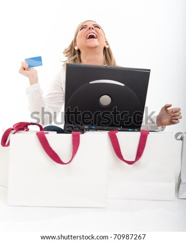 Exstatic young blond woman holding a credit card in front of a computer surrounded by shopping bags - stock photo