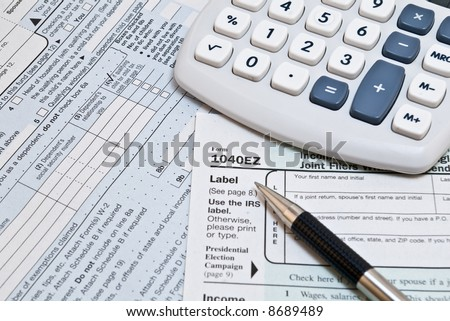 1040EZ income tax forms with pen and calculator - stock photo