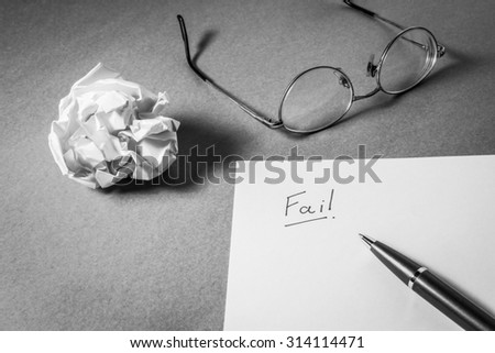 """""""Fail"""" hand writing on paper, glasses pen and crumpled paper. Business frustrations, Job stress and Failed exam concept. Black and white filter. - stock photo"""