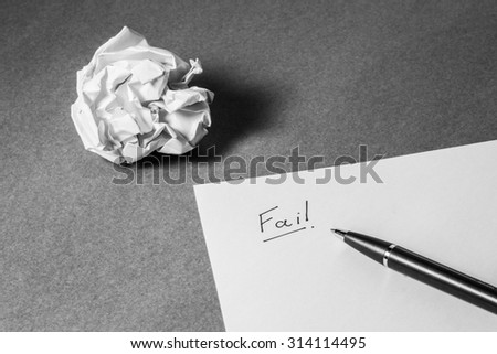 """""""Fail"""" hand writing on paper, pen and crumpled paper. Business frustrations, Job stress and Failed exam concept. Black and white filter.  - stock photo"""