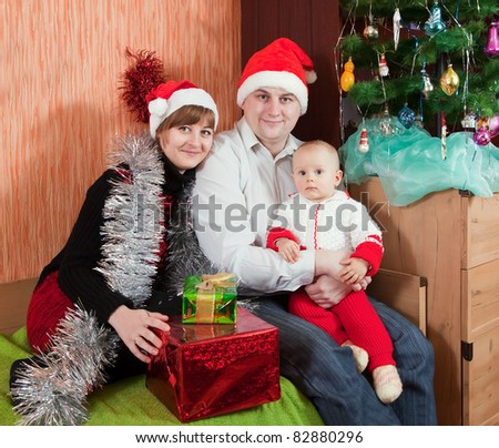 family from three at  home with  Christmas tree
