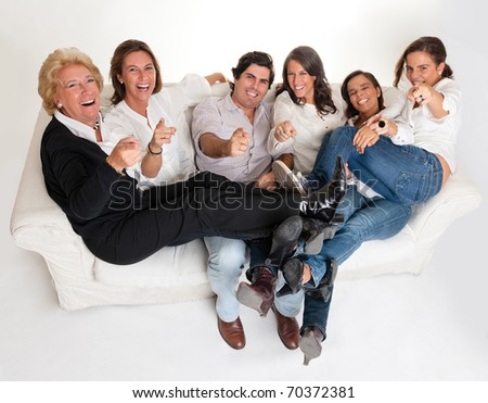 Family group sitting on a sofa laughing and pointing to the camera - stock photo