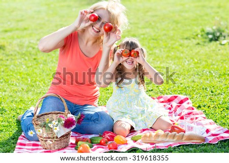 Family having fun while picnicking in summer park - stock photo