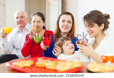 family having tea with cakes at home  together
