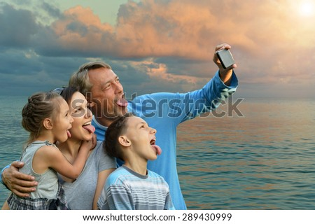 family of four on a background of a seashore put out one's tongue - stock photo