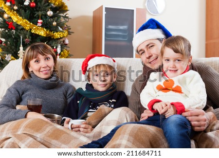 family of four on sofa against Christmas tree  at home