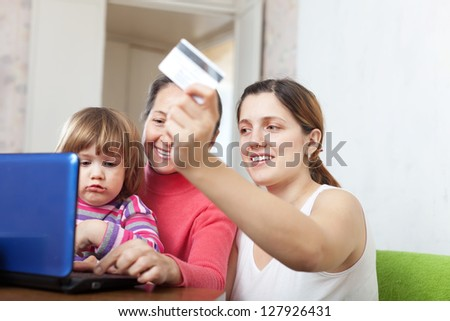 Family of three generations buying online with laptop and credit card  in living room - stock photo