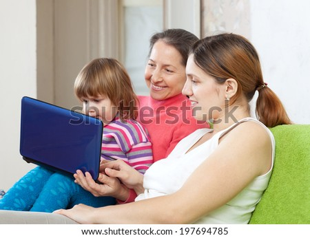 Family of three generations looks the netbook in home interior - stock photo