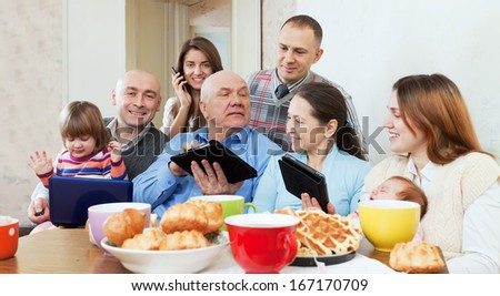 family of three generations or group of friends with electronic devices  - stock photo